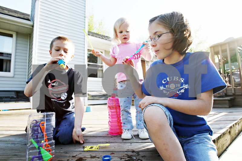 Rob Winner – rwinner@daily-chronicle.com<br /> <br /> Danny Earl (from left), 8, Alex Earl, 1, and Emily Earl blow bubbles outside together at their home in DeKalb, Ill. on Thursday April 30, 2010.