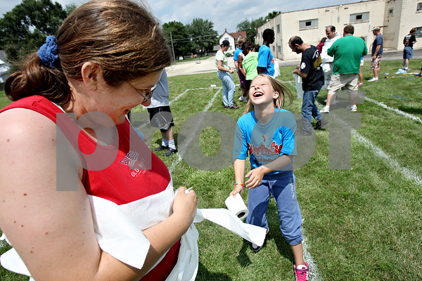 Rob Winner – rwinner@daily-chronicle.com<br /> <br /> Sarah Bullmer (left) is wrapped up by Tessa Wallace, 11, with toilet paper during a mummy wrap contest at the Opportunity House in Sycamore, Ill. on Tuesday July 27, 2010. Members of the Kishwaukee Family YMCA visited the Opportunity House for a day of competition.