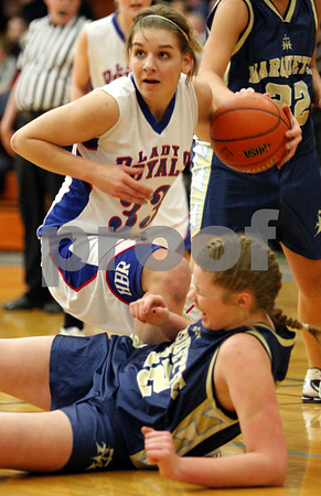 Rob Winner – rwinner@daily-chronicle.com<br /> Hinckley-Big Rock's Tess Godhardt (top) moves the ball over and past Ottawa Marquette's Cordella Murphy on the way to the basket during the first quarter.