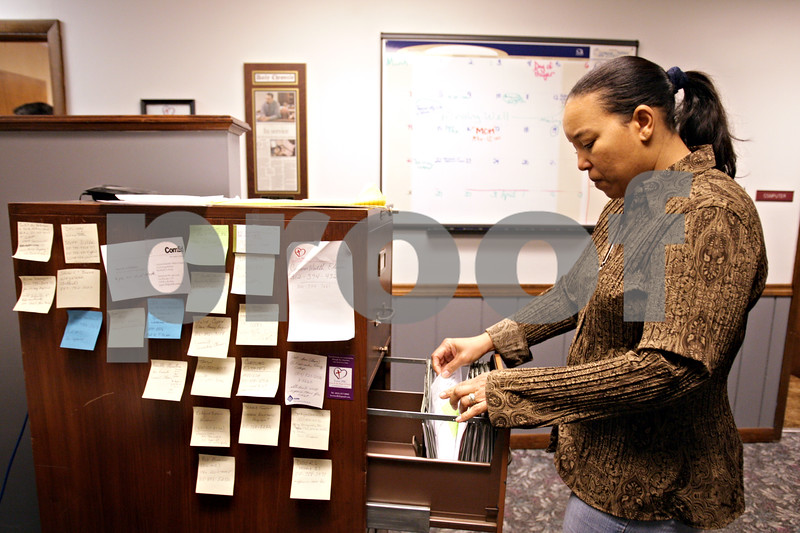 Beck Diefenbach  -  bdiefenbach@daily-chronicle.com<br /> <br /> Volunteer Erica Scott talks looks through client records in the offices of Love INC in DeKalb, Ill., on Thursday March 11, 2010.
