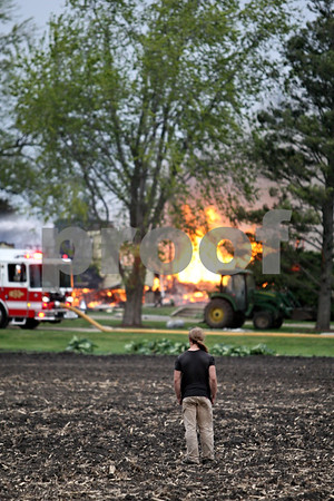 Beck Diefenbach  -  bdiefenbach@daily-chronicle.com<br /> <br /> Tim McPartland looks on at the Watson home burns in rural DeKalb, Ill., on Friday April 30, 2010.