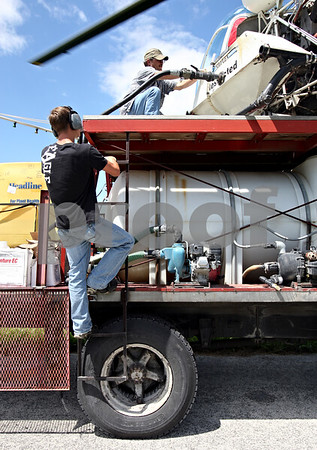 Rob Winner – rwinner@daily-chronicle.com<br /> <br /> William Henley (top) refills a crop dusting helicopter with fungicide while the team of workers from Hendrickson Flying Service, located in Rochelle, sprays farm fields near Fenstermaker and Barber Greene roads in Cortland Township on Friday July 23, 2010.