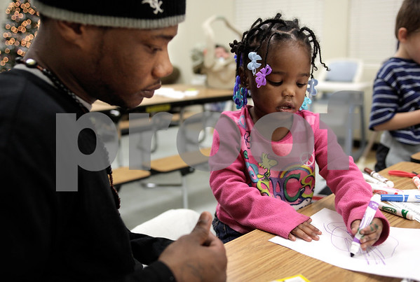 Kyle Bursaw – kbursaw@daily-chronicle.com<br /> <br /> Tyjaya Frierson, 2, color her uncut snowflake as her father Tywan looks on at Hope Haven in DeKalb, Ill on Thursday, Dec. 9, 2010.
