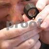Kyle Bursaw – kbursaw@daily-chronicle.com<br /> <br /> Aaron Brunson, of The Gold Refinery, looks through a loupe to find a stamp indicating how many karats a gold piece of jewelry is, at The Gold Refinery stand in Kishwaukee Hospital in DeKalb, Ill. on Nov. 12, 2010. After appraising all the pieces of gold and silver, Brunson awarded the client with $100.