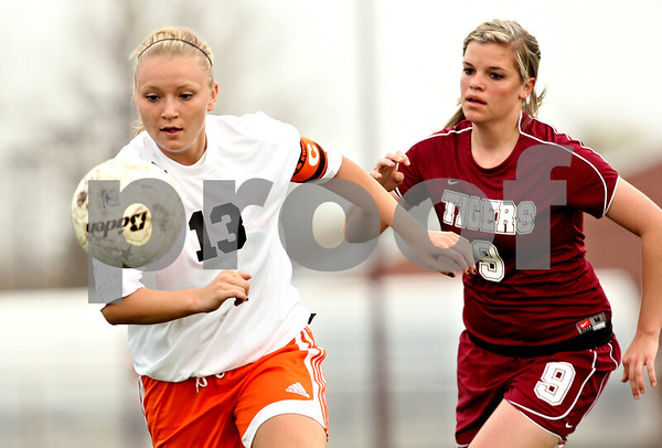 Beck Diefenbach  -  bdiefenbach@daily-chronicle.com<br /> <br /> DeKalb's Kay Smith (13, left) kicks the ball ahead of Plainfield North's Katie Cox (9) during the first half of the game at DeKalb High School in DeKalb, Ill., on Monday April 12, 2010. Plainfield North defeated Dekalb 4 to 1.