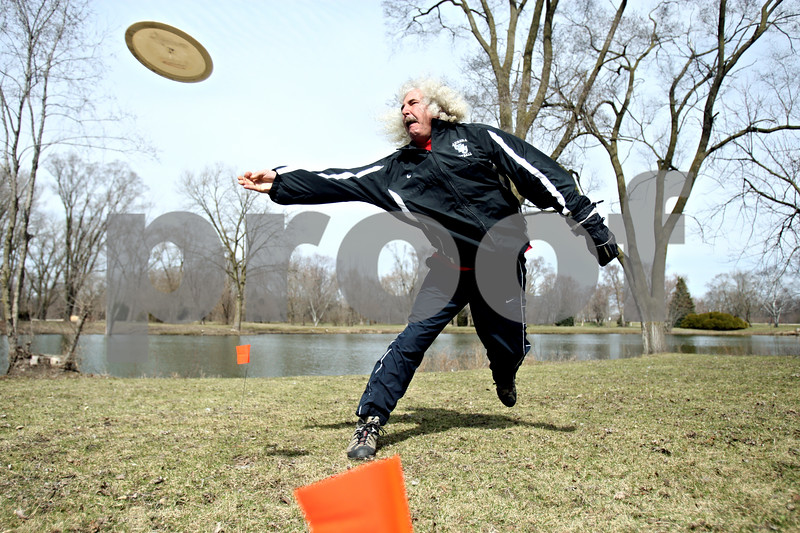 """Rob Winner – rwinner@daily-chronicle.com<br /> <br /> DeKalb County Disc Golf Club member Randy Moore Sr., of Oswego, takes a practice throw at Pioneer Park in Kirkland, Ill. on Saturday March 27, 2010. The club recognized outstanding members of their winter league, which ran from November to March, with """"thropies,"""" made by Northern Illinois University glassblower Jason Gordon. The club's summer league begins April 2 and will meet every Friday at 5 p.m. For more information visit  <a href=""""http://www.dcdisc.ning.com"""">http://www.dcdisc.ning.com</a>."""