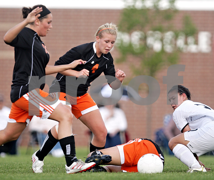 Beck Diefenbach  -  bdiefenbach@daily-chronicle.com<br /> <br /> DeKalb's Jennifer Dorland (14, far left) and Cara Sisler (4, center) and Sycamore's Emma Norris (7, far right) eye a loose ball during the second half of the IHSA Class 2A Rochelle Regional Championship at Rochelle Township High School in Rochelle, Ill., on Friday May 21, 2010. Sycamore defeated DeKalb 2 to 1.