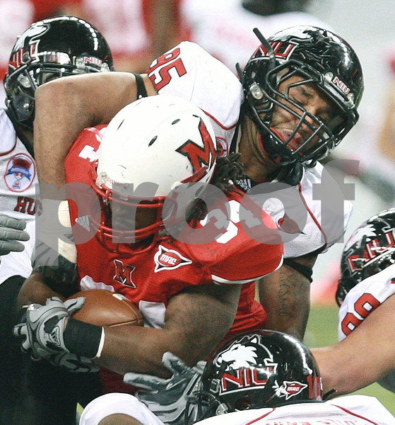 Kyle Bursaw – kbursaw@daily-chronicle.com<br /> <br /> Northern Illinois defensive end Sean Progar (95) wraps up Miami (OH) running back Thomas Merriweather (34) in the fourth quarter of the MAC Championship game. The Miami (OH) defeated Northern Illinois 26-21 at Ford Field in Detroit, Mich. on Friday, Dec. 3, 2010.