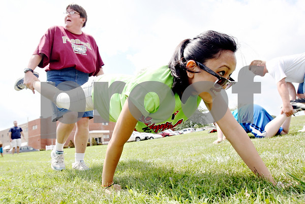 Rob Winner – rwinner@daily-chronicle.com<br /> <br /> Sheila Buchholz (left) holds the legs of Nikki Torres during a wheel barrel race at the Opportunity House in Sycamore, Ill. on Tuesday July 27, 2010. Members of the Kishwaukee Family YMCA visited the Opportunity House for a day of competition.