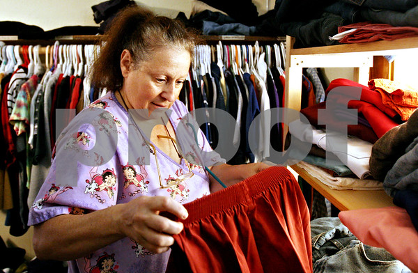 "Rob Winner – rwinner@daily-chronicle.com<br /> <br /> DeKalb resident Linda Maffei looks through items of clothing at the Blessing Well of the First Church of the Nazarene in DeKalb, Ill. on Wednesday August 11, 2010. ""It's about the emotional support as much as the food and clothes,"" said Maffei about the volunteers who help at the Blessing Well."