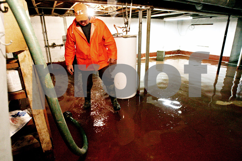 Rob Winner – rwinner@daily-chronicle.com<br /> <br /> A village of Waterman employee checks out the flooded basement of a home located on the 300 block of North Maple Street in Waterman, Ill. on Thursday May 13, 2010.