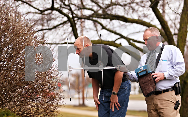 Beck Diefenbach  -  bdiefenbach@daily-chronicle.com<br /> <br /> Using a Care Trak radio telemetry-based locator, DeKalb County Sheriff deputies Gary Dumdie, left, and Brad Carls train to find a missing person outside the county administration building in Sycamore, Ill., on Thursday March 11, 2010. The Care Trak system is meant to track individuals at risk with wandering.