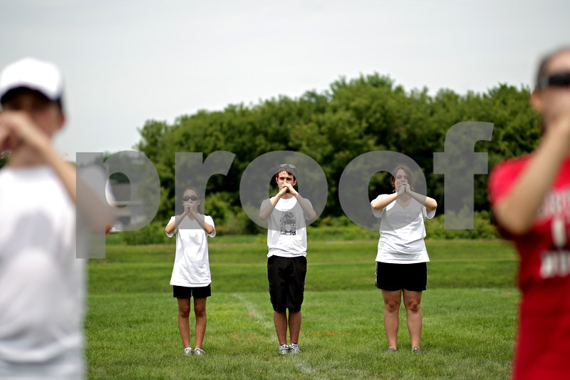 Beck Diefenbach  -  bdiefenbach@daily-chronicle.com<br /> <br /> From left, sophomore Theresa Nguyen, senior Richard Hartman and freshman Amy Clark stand at attention with imaginary instruments as they practice marching techniques during DeKalb High School's band camp at Clinton Rosette Middle School in DeKalb, Ill., on Monday August 2, 2010.