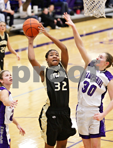 Beck Diefenbach  -  bdiefenbach@daily-chronicle.com<br /> <br /> Sycamore's Michelle Todd (32, left) shoots the ball during the third quarter of the IHSA Class 3A Regional game at Rochelle Township High School in Rochelle, Ill., on Wednesday Feb. 17, 2010