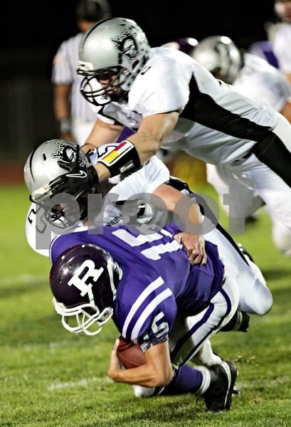 Beck Diefenbach – bdiefenbach@daily-chronicle.com<br /> <br /> Rochelle's Nicke Moore (15, bottom) is taken down by Kaneland linebacker Sean Carter (25, middle) and Blake Serpa (2, top) during the second quarter of the game against Rochelle at Rochelle High School in Rochelle, Ill., on Friday sept. 24, 2010.