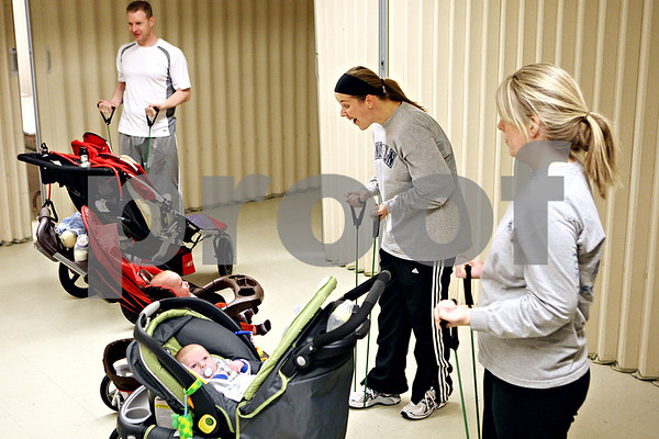 Rob Winner – rwinner@daily-chronicle.com<br /> Corrie Dyre, of Rochelle, smiles at her baby Lucas, 3 months, while participating in a work out program called Stroller Strides in the basement of Immanuel Lutheran Church in DeKalb, Ill. on Saturday January 9, 2010.