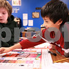 Kyle Bursaw – kbursaw@daily-chronicle.com<br /> <br /> Tristen Tran, a fifth-grader at North Elementary in Sycamore, moves his piece in a board game called 'Get Connected' as fellow classmate Nathan Flaherty, left, looks on. The game, part of the Junior Achievement program, shows students that you can 'win' by learning new technologies.