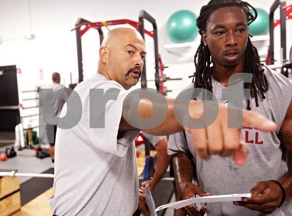 Beck Diefenbach - bdiefenbach@daily-chronicle.com<br /> <br /> Strength and conditioning coach Eric Klein, left, explains part of the workout regiment to defensive end Darnell Bolding at the Yordon Center on the Northern Illinois University Campus in DeKalb, Ill., on Tuesday Aug. 10, 2010.