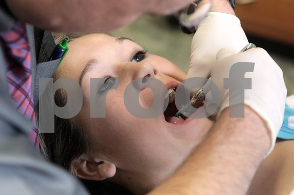 Kyle Bursaw – kbursaw@daily-chronicle.com<br /> <br /> Dr. Todd Curtis makes adjustments to a spacer in the mouth of Drew Moulton, 13, in his Sycamore office. Though Moulton still has baby teeth, the procedure will help correct spacing in her adult teeth. <br /> <br /> 12/09/10