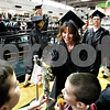 Rob Winner – rwinner@daily-chronicle.com<br /> <br /> On her way to the stage, Christina Crome is given flowers by her sons Derrick (left), 10, and Brayden, 8, before receiving her diploma during the Kishwaukee College commencement ceremony on Saturday May 15, 2010 in Malta, Ill.