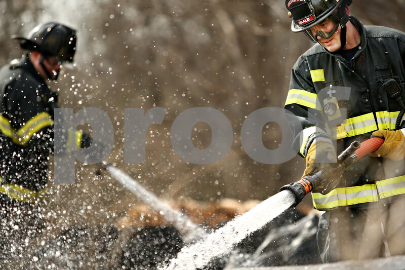 Beck Diefenbach  -  bdiefenbach@daily-chronicle.com<br /> <br /> DeKalb firemen soak charred wood with water after the small area caught on fire on a lot at South First Street in DeKalb, Ill., on the afternoon of Friday April 2, 2010.