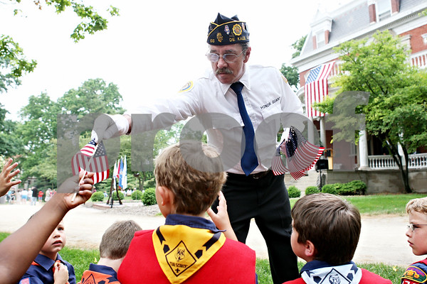 Rob Winner – rwinner@daily-chronicle.com<br /> <br /> Harry Begovich, of American Legion Post 66, hands out flags to some scouts outside the Ellwood House on Monday May 31, 2010 in DeKalb, Ill.