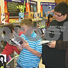Dana Herra dherra@daily-chronicle.com<br /> <br /> Jared Brown, 13, looks over the shoulder of John Hermes, 12, as he reads a book at Camelot School's first book fair on Friday. The book fair continues through Tuesday.