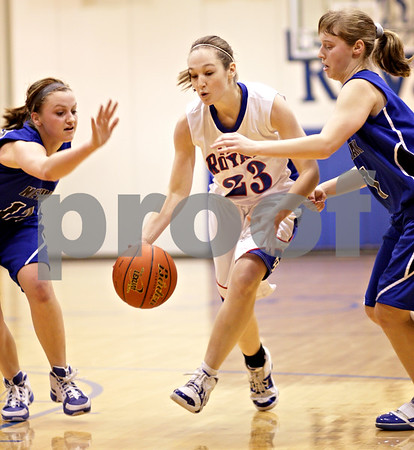 Beck Diefenbach  -  bdiefenbach@daily-chronicle.com<br /> <br /> Hinckley-Big Rock's Alyssa Baunach (23, center) dribbles between Newark's Katie Larson (12, left) and Lauren McNanna (1) during the first quarter of the game at H-BR High School in Hinckley, Ill., on Thursday Jan. 14, 2010. H-BR defeated Newark 46 to 30.