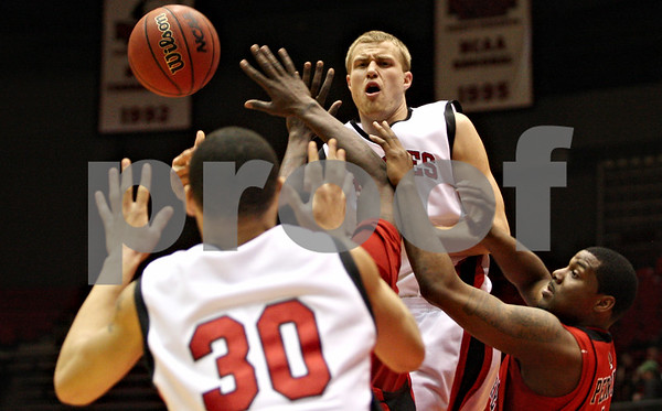 Rob Winner – rwinner@daily-chronicle.com<br /> Northern's Sean Kowal (right) passes to teammate Lee Fisher (30) under the Huskies' basket during their game against Ball State in the second half on Saturday February 13, 2010 in DeKalb, Ill. Ball State defeated NIU, 71-66.
