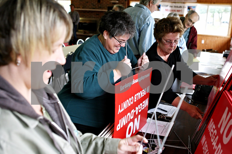Rob Winner – rwinner@daily-chronicle.com<br /> <br /> Heather Adams (from left), Lisa Wilcox and Linda Whipple assemble signs against the proposed landfill expansion in DeKalb county at the Cortland Lions Club in Cortland, Ill. on Saturday October 2, 2010.