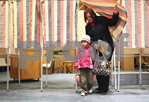 Rob Winner – rwinner@daily-chronicle.com<br /> Michele Stieren and her daughter Grace, 3, exit a voting booth at Westminster Presbyterian Church in DeKalb, Ill. on Tuesday February 2, 2010.