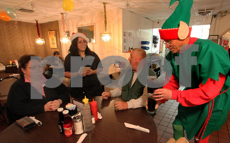 Wendy Kemp - For The Daily Chronicle<br /> Volunteer Tom Riley (right) brings drinks while owner Maria Morrow takes an order from customers Rose Wakefield (left) and her husband Pat, of DeKalb, during the complimentary holiday dinner at Flippin' Eggs in DeKalb on Thursday.<br /> DeKalb 12/23/10