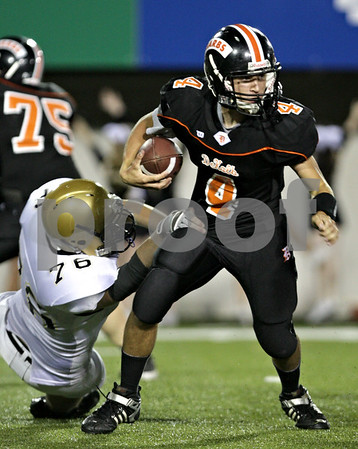 Beck Diefenbach – bdiefenbach@daily-chronicle.com<br /> <br /> DeKalb quarterback Bobby Russell (4) attempts to shake off a defender during the fourth quarter of the Castle Challenge game between DeKalb and Sycamore High Schools at Huskie Stadium on the campus of Northern Illinois University in DeKalb, Ill., on Friday Sept. 10 2010.