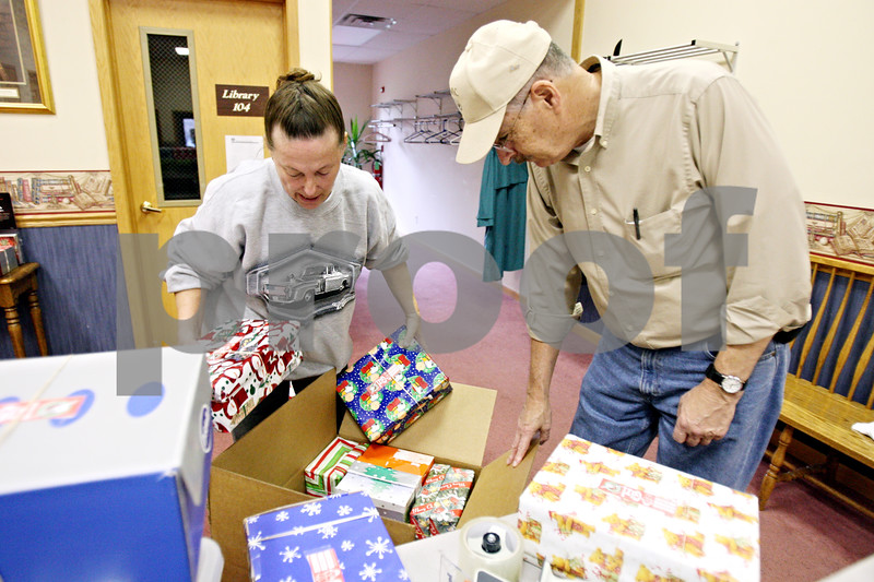 Rob Winner – rwinner@daily-chronicle.com<br /> <br /> At First Baptist Church of Sycamore on Monday afternoon, volunteers for Operation Christmas Child, including Deb Byrd (left) and John Peters, load a shipping box with smaller boxes filled with gifts which will be distributed to millions of children throughout the world for Christmas.
