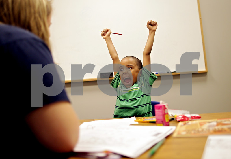 """Beck Diefenbach  -  bdiefenbach@daily-chronicle.com<br /> <br /> Jahmir Mojica, 5, reacts after correctly writing the letter """"G"""" during a reading and writing tutoring session with Lauren Olson (left) at the Northern Illinois University Literacy Clinic in DeKalb, Ill., on Wednesday July 14, 2010."""