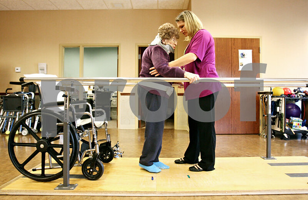 Rob Winner – rwinner@daily-chronicle.com<br /> <br /> DeKalb resident Amanda Mitrovic (left) works on a balancing exercise with help from JoAnne Mata, the director of rehab, at the Pine Acres Rehab and Living Center in DeKalb on Tuesday.