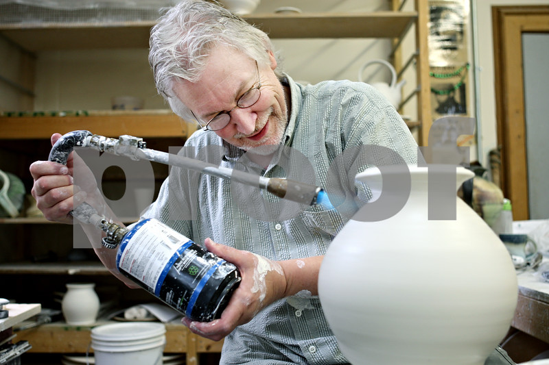 Rob Winner – rwinner@daily-chronicle.com<br /> <br /> Steven Hill of Center Street Clay in Sandwich, Ill. uses a torch while working on one of his pieces on Tuesday July 20, 2010.