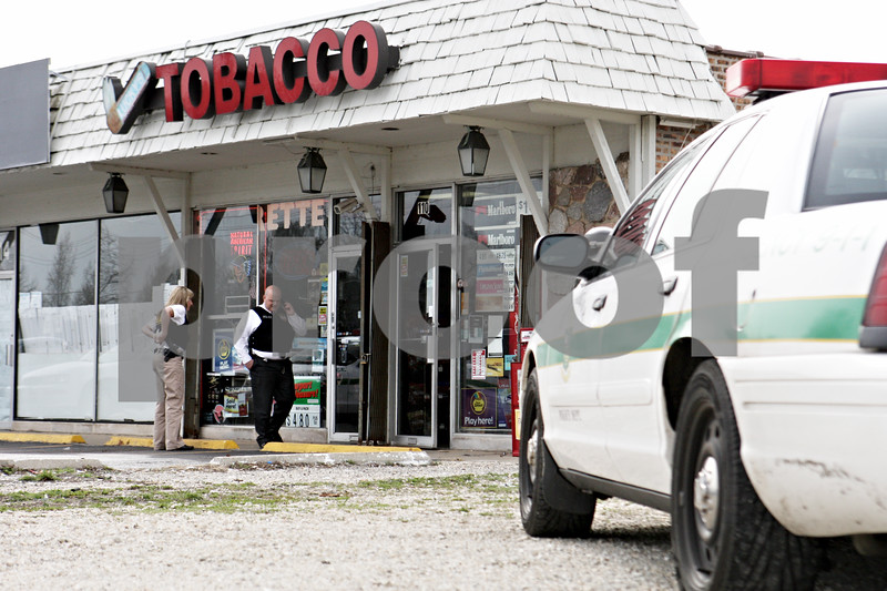 Rob Winner – rwinner@daily-chronicle.com<br /> <br /> Officers from the DeKalb Police Department investigate Lucky's Tobacco after a robbery at the business on Friday April 2, 2010 in DeKalb, Ill.