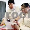 Rob Winner – rwinner@daily-chronicle.com<br /> Jinhee Kim helps her daughter, Ashley, 13, with her homework at Genoa Cleaners in Genoa, Ill. on Thursday February 11, 2010. Ashley became paralyzed from the waist down after a swimming accident on September 12, 2009.