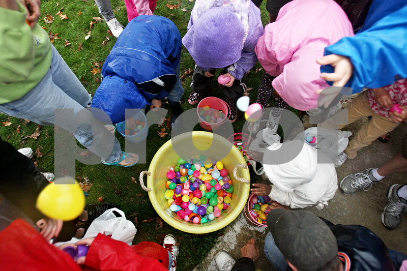 Rob Winner – rwinner@daily-chronicle.com<br /> <br /> Children and parents toss plastic eggs into a tub after emptying them of candy after an Easter egg hunt at Hopkins Park in DeKalb, Ill. on Saturday April 3, 2010.