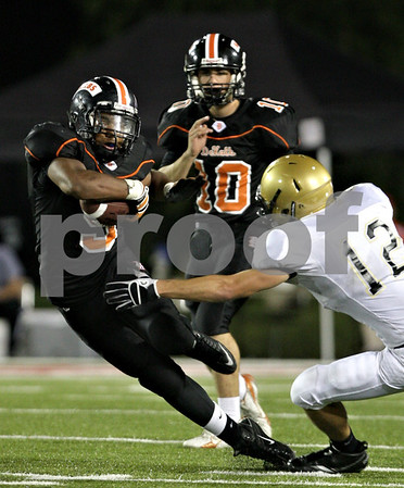 Beck Diefenbach – bdiefenbach@daily-chronicle.com<br /> <br /> DeKalb's Spencer Blank-Jones (5, left) attempts to slip past the reach of Sycamore's Trevor Methey (12, right) during the third quarter of the Castle Challenge game between DeKalb and Sycamore High Schools at Huskie Stadium on the campus of Northern Illinois University in DeKalb, Ill., on Friday Sept. 10 2010.