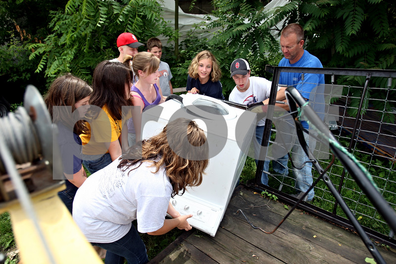 Rob Winner – rwinner@daily-chronicle.com<br /> <br /> A group of youths, from sixth grade through high school, who are members of United Church of Christ in Shabbona, Ill. place a washer onto a trailer on Friday June 11, 2010. The group has been collecting metals for recycling in order to fund church camp for this summer.