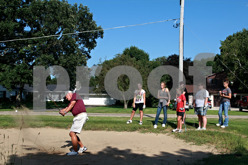 Beck Diefenbach - bdiefenbach@daily-chronicle.com<br /> <br /> Indian Creek girls golf coach Keith Haeg (far left) demonstrates chipping out of a bunker to his team during practice at the Indian Oaks Golf Course in Shabbona, Ill., on Wednesday Aug. 18, 2010.