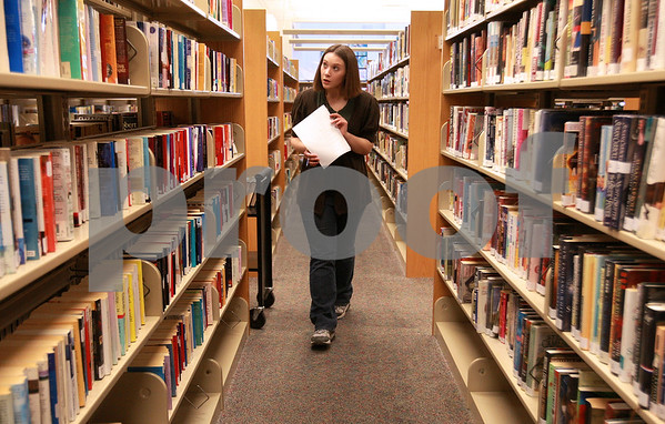 Kyle Bursaw – kbursaw@daily-chronicle.com<br /> <br /> Justine LaRoche, a circulation assistant at the Sycamore public library, searches the stacks for books that have been requested at other libraries on Tuesday, Dec. 28, 2010. This practice is part of the inter-library loan system.