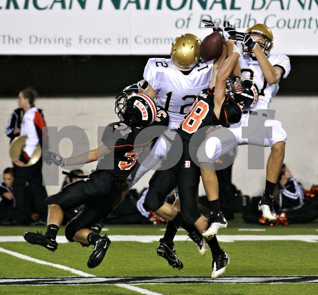 Beck Diefenbach – bdiefenbach@daily-chronicle.com<br /> <br /> (From left) DeKalb's Trevor Bonney (31), Sycamore Trevor Mathey (12), DeKalb's Jake Jones (28) and Sycamore's Jake Turner (81) all leap for the ball during the second quarter of the Castle Challenge football game between DeKalb and Sycamore High Schools at Huskie Stadium on the campus of Northern Illinois University in DeKalb, Ill., on Friday Sept. 10 2010.