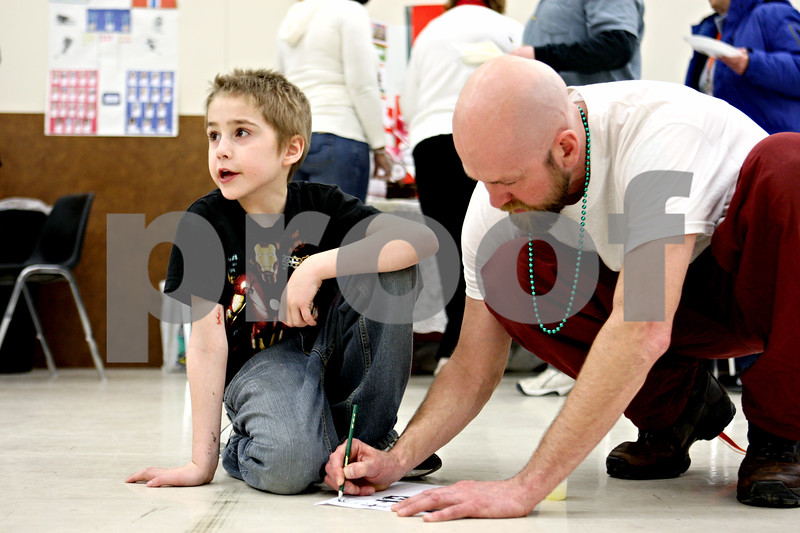 Rob Winner – rwinner@daily-chronicle.com<br /> D.J. Janssen, 7, and teacher John Panek work together on a scavenger hunt to identify the flags of nations from around the world at Camelot School in DeKalb, Ill. on Friday February 26, 2010. Students at Camelot have spent the last two weeks learning all about the winter olympics.