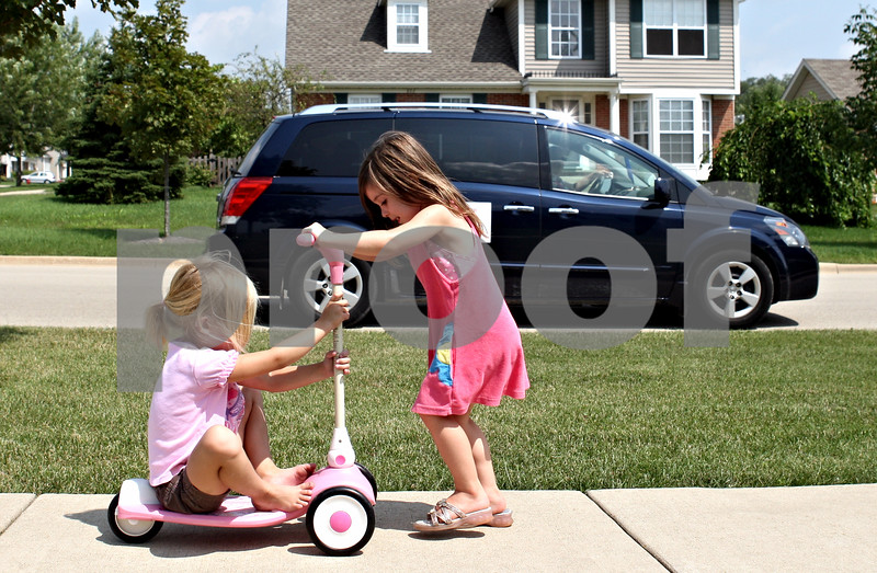 Rob Winner – rwinner@daily-chronicle.com<br /> <br /> DeKalb residents Audrey Minalga (left), 4, and  Julia Gavin, 3, play on the sidewalk near the intersection of Kensignton Boulevard and Bush Street in DeKalb, Ill. on Friday August 6, 2010. Recently, a group of residents living in Kensington Pointe subdivision in DeKalb petitioned to have a traffic study done to make a four-way stop at the intersection.