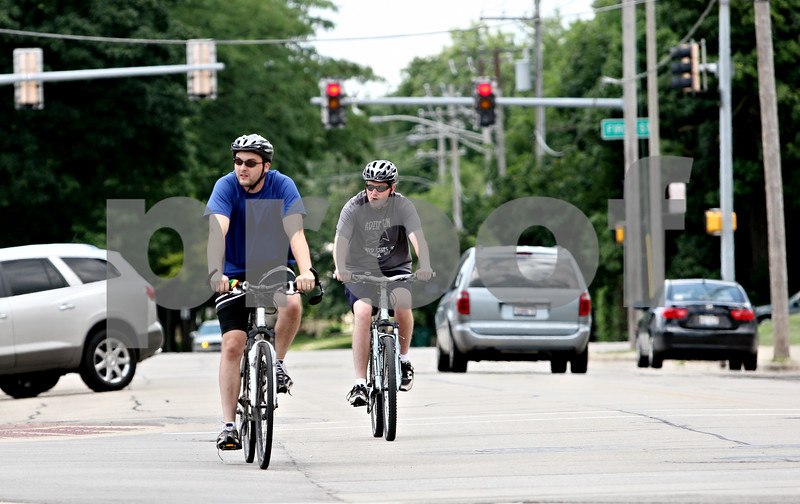 Rob Winner – rwinner@daily-chronicle.com<br /> <br /> Cyclists Jonathon Merritt (left) and Jeff Craig, both of DeKalb, cruise past the intersection of Locust Street and Second Street in DeKalb, Ill. on Thursday July 8, 2010 on their way to Sycamore.