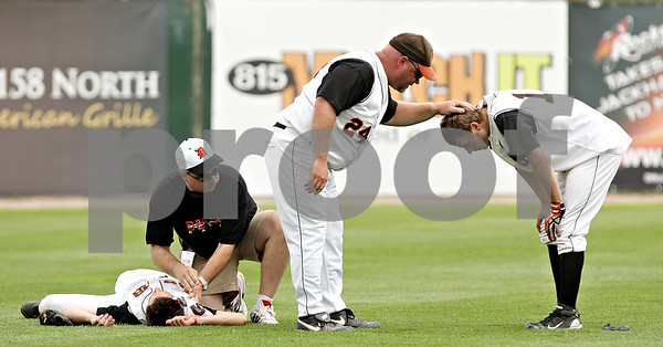 Beck Diefenbach  -  bdiefenbach@daily-chronicle.com<br /> <br /> Head coach Justin Keck (center) checks on DeKalb's Jake Gordon (right) as Brian Sisler (left) is tended to during the first inning of the IHSA Class 3A State Semifinal Game against Marian Central in Joliet, Ill., on Friday June 11, 2010.