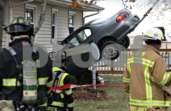 Kyle Bursaw - kbursaw@daily-chronicle.com<br /> <br /> Firefighters look on as a Chevy Malibu is hoisted out of the home at 2972 Route 23, just south of Genoa.